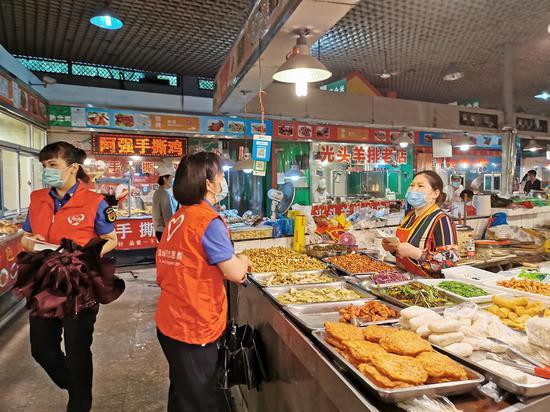志愿者团队向约两百户市场经营主体做了垃圾分类的专项宣传。 温州市综合行政执法局供图
