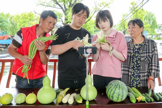 """志愿者在中道村幫扶基地帶領群眾一起""""擺地攤、搞直播""""打開綠色蔬菜銷路  譚云俸 攝"""