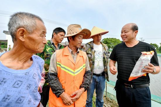 志愿者在七斗漾合作社基地指導當季河蟹飼料配料  譚云俸 攝
