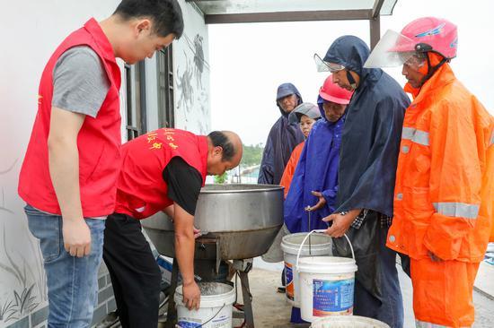志愿者在七斗漾合作社基地指導扶貧對象搭配河蟹飼料  譚云俸 攝