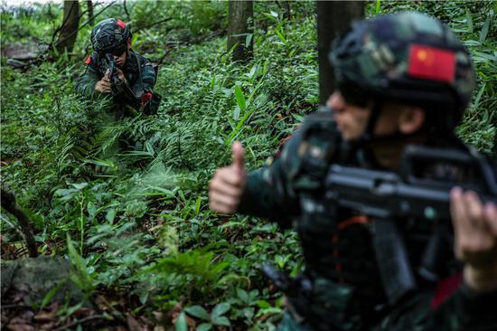 特战队员在演练中使用战术手语相互沟通。  胡港 摄