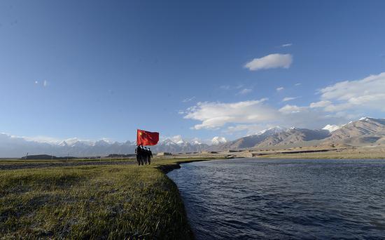 6月20日,民警正在沿着高原河流巡逻。(孔志勇 摄)