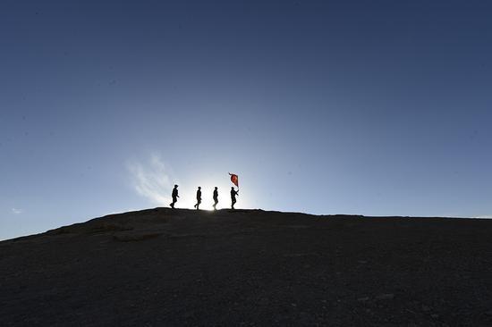 6月20日,民警在夕阳下沿着山脊巡逻。(孔志勇 摄)