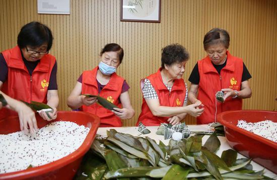 杭州江干区景芳社区志愿者在包粽子。  李子光(通讯员) 摄
