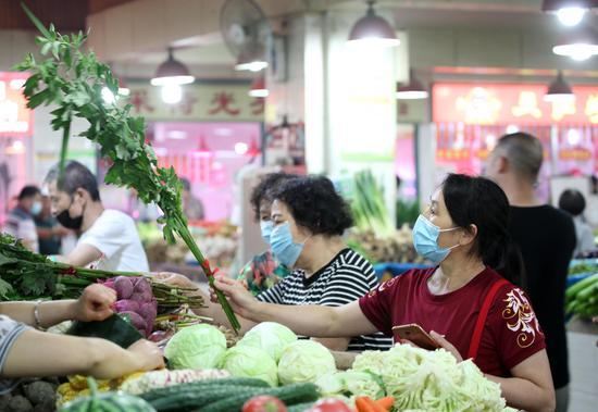 一位市民在农贸市场内选购艾草。  李子光(通讯员) 摄