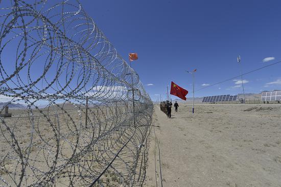6月21日,民警带领护边员巡查一线铁丝网。(孔志勇 摄)