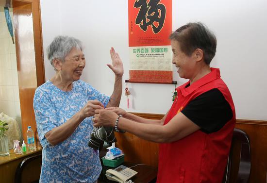 杭州江干区景芳社区志愿者向独居老人赠送包好的粽子。  李子光(通讯员) 摄