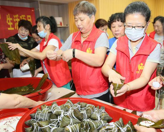 杭州江干区景芳社区志愿者一同包粽子。  李子光(通讯员) 摄