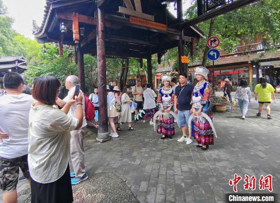 图为游客在西江千户苗寨景区游玩。 岳旺 摄