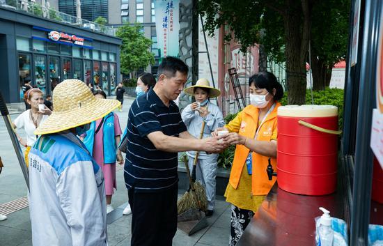 志愿者正在为来往居民送凉茶。闵峰摄