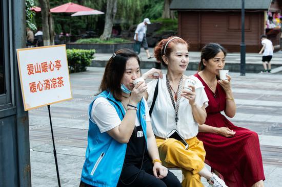 志愿者为爱山广场的环卫工人送凉茶。闵峰摄