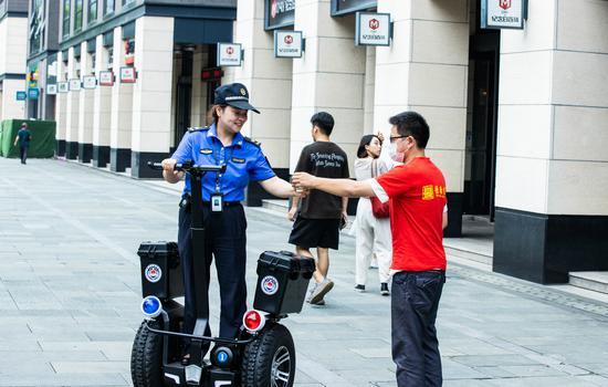 志愿者为正在巡逻的执法队员送凉茶。闵峰摄