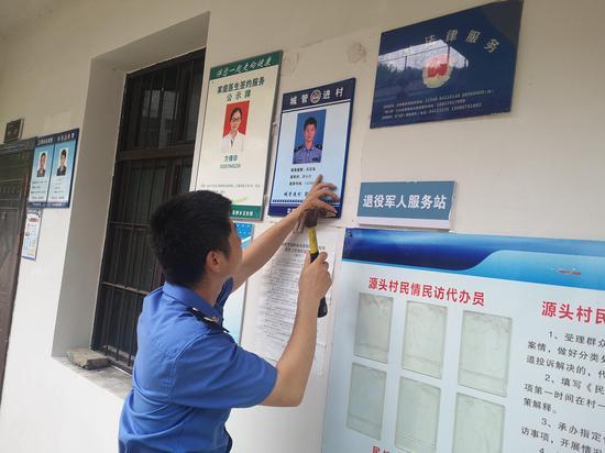 """浦江县综合行政执法局在村公开栏张贴""""一村一城管""""联系牌。 周彦 摄"""