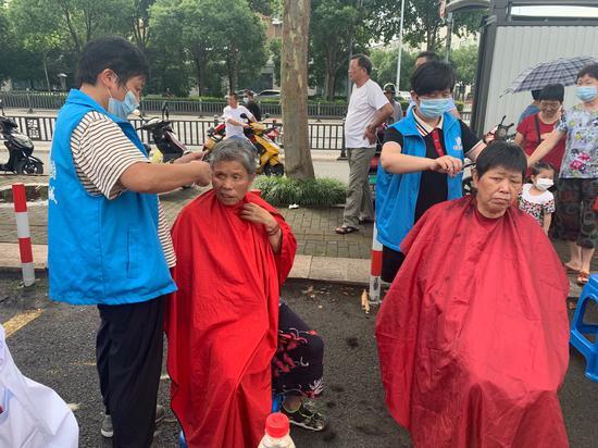 志愿者为老人剪发。  越城宣传部提供