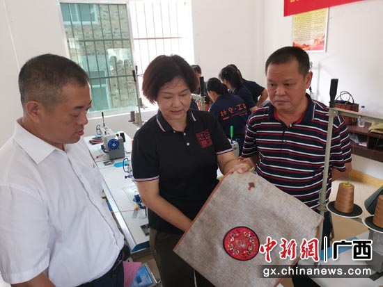广西金壮锦文化艺术有限公司董事长贺卡向南宁市青秀区人民政府副区长孙凯(左一)展示学员作品成果。