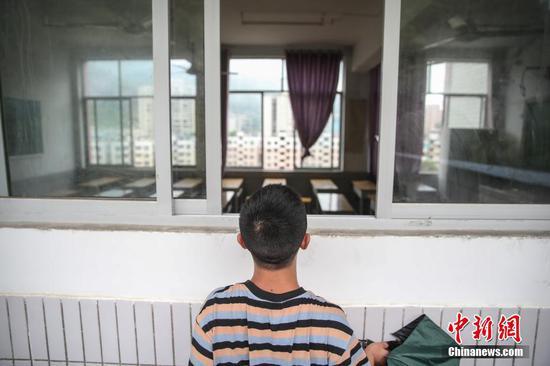 一名考生在眺望考场座位安排,因疫情防控考场不允许考生进入。 瞿宏伦 摄