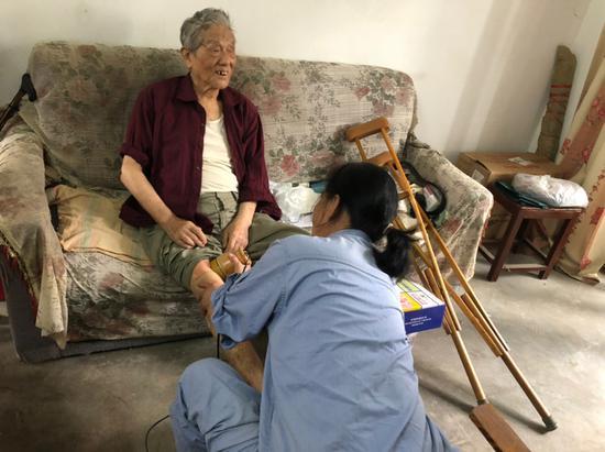 林丽帮老人按摩腿部。镇海宣传部供图