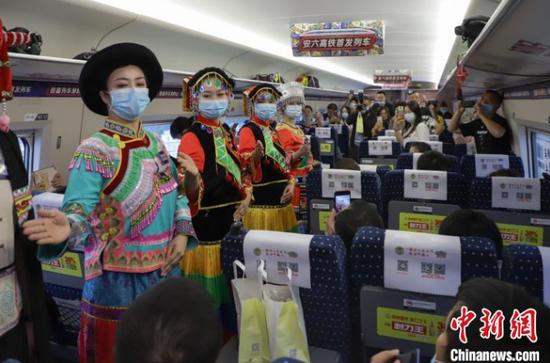 图为穿着少数民族服饰的列车乘务员在车厢内进行礼仪展示。 岳旺 摄