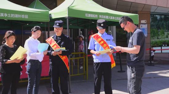 阿勒泰边境管理支队吐尔洪边境派出所民警在景区售票大厅前宣传边境法律法规。