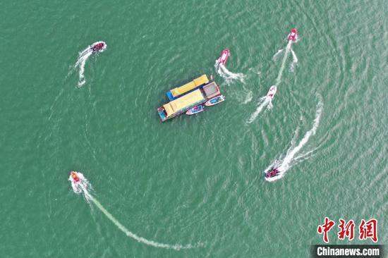 图为消防救援人员正在利用救生艇围绕事故船只进行人员搜救(无人机拍摄)。 李兴文 摄