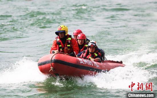 图为消防救援人员乘坐救生艇进行人员搜救。 李兴文 摄