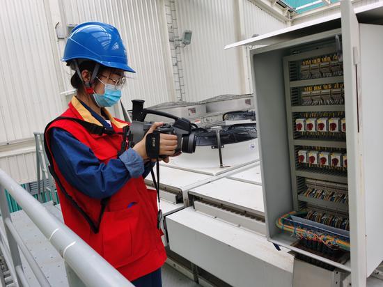 图为±1100KV昌吉换流站工作人员在大负荷来临前对为空冷棚进行巡检及端子箱红外测温。
