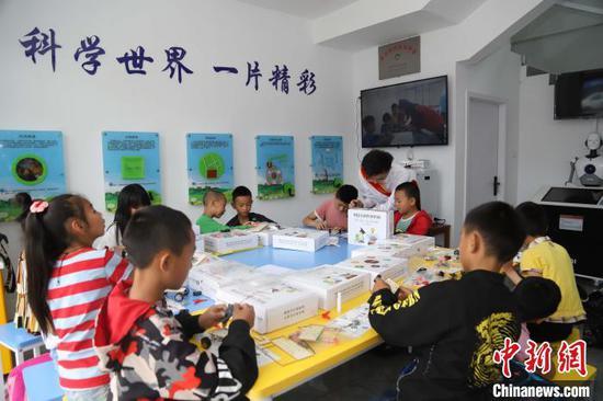 图为孩子们在青少年科学工作室制作手工模型。 岳旺 摄