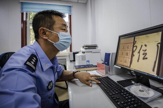 """民警对测试考核""""笔迹""""进行仔细检测比对。李国贤"""