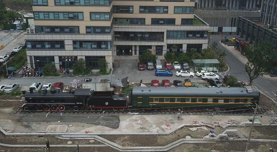 一辆老火车停在一幢大楼前。  王刚 摄