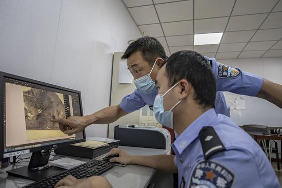"""民警对测试考核""""指纹""""进行仔细检测。李国贤"""