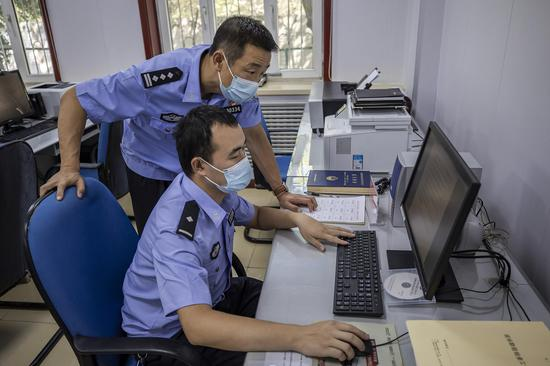 """民警对测试考核""""足迹""""进行仔细比对。李国贤"""