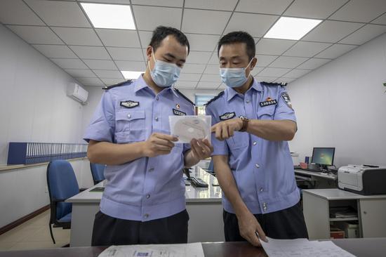 民警对《全国公安机关刑事技术实验室能力验证(盲测)工作》测试光盘进行仔细核对。李国贤