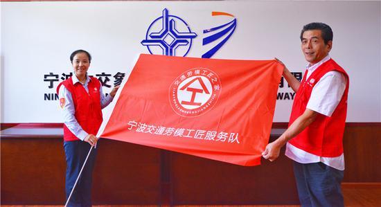 劳模陈霞娜和夏慧星展示队旗。 宁波市交通运输工会提供