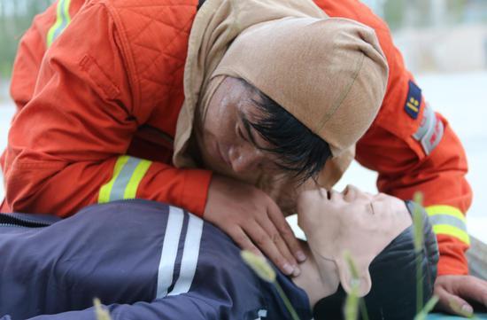 中队长寇作龙进行心肺复苏训练,判断伤员有无意识。