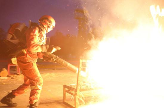 消防员陈书昊正在扑打模拟火线。