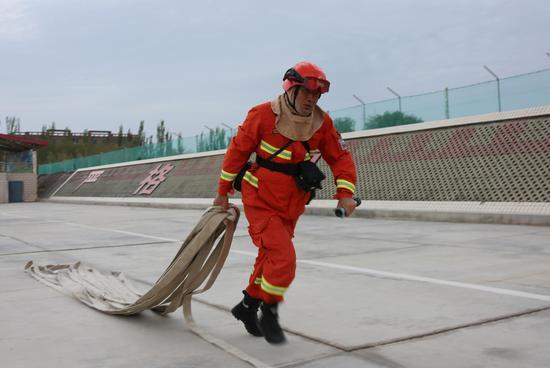水泵架设与撤收科目中消防员正在进行撤收管带。