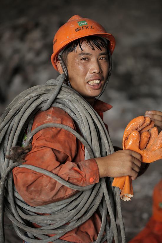 义东高速西甑山隧道出洞口,一名焊工衣服被汗水打湿。亚星集团省交通集团杭金衢公司供图