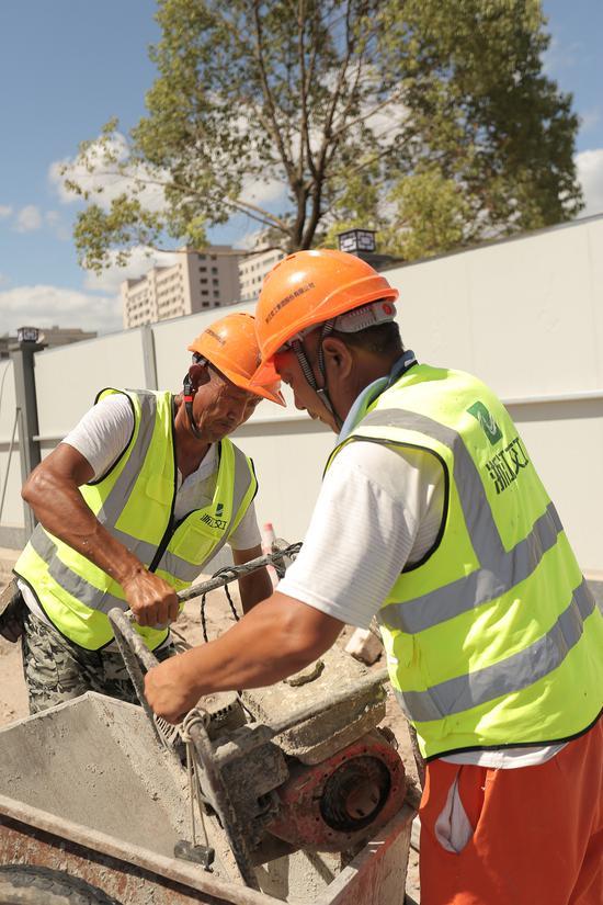 义东高速一线建设者正头顶烈日进行混凝土浇捣工作业。亚星集团省交通集团杭金衢公司供图