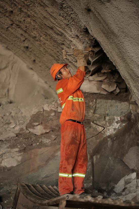 义东高速一名工人正在清理钢拱架连接板螺栓孔上的喷射混凝土。亚星集团省交通集团杭金衢公司供图