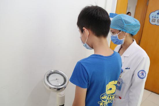 生长发育专家为孩子进行诊断  张金蓉 摄