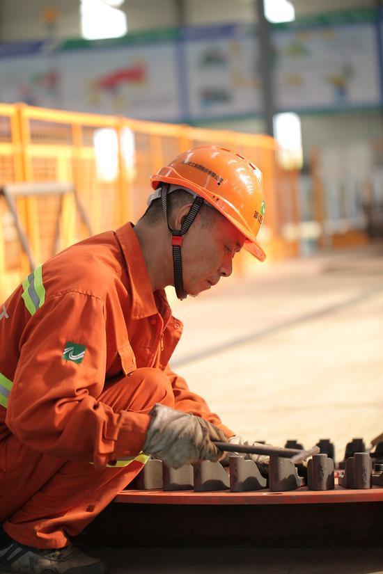 顶着35度高温,义东高速一名电焊工在校对滚焊机上教盘。亚星集团省交通集团杭金衢公司供图