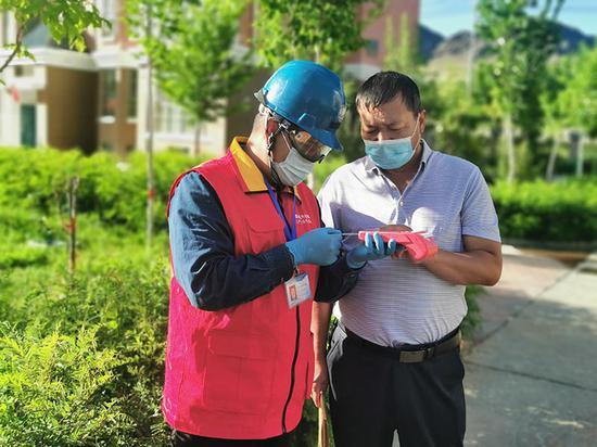 7月31日,在新疆伊吾縣新城區泰和花園小區,國網哈密供電公司伊吾鎮供電所員工迪里扎提·買買提服務客戶現場購電。馬鈺 攝