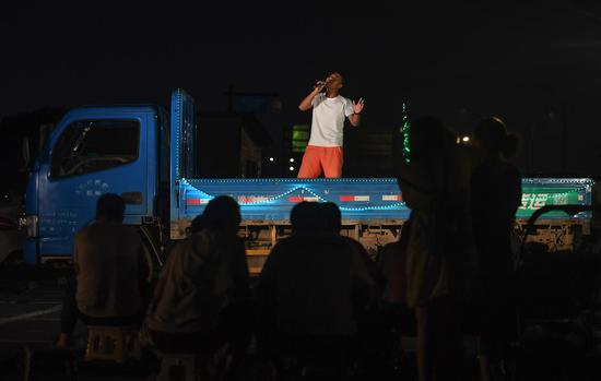 一位貨運司機在車廂上放聲高歌。  王剛 攝