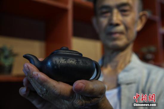 """胡正德展示自己制作的""""黑砂陶""""茶壺。中新社記者 瞿宏倫 攝"""