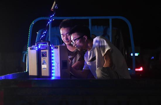 貨運司機和工作人員在車廂上調試音響設備。  王剛 攝