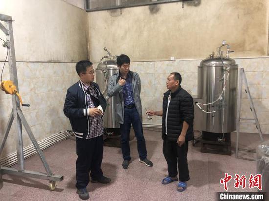 李磊(左)在從江縣丙妹鎮煨酒項目與企業工作人員交流。 受訪者本人 供圖