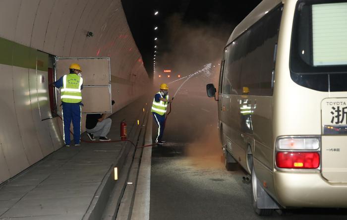 """市政养护工作人员打开隧道消防设备对""""起火车辆""""进行灭火。杭州市路桥集团供图"""