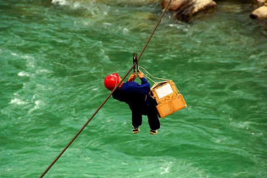 """2007年,中國移動在獨龍江鄉開展""""村村通電話工程""""建設。圖為移動員工用溜索運送建站物資。"""