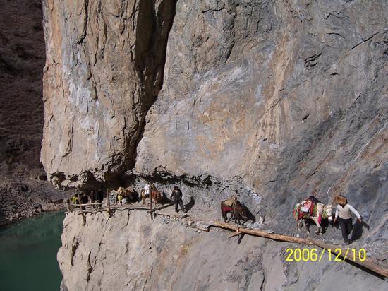 在西藏昌都,中國移動運送基站設備的馬隊依托金沙江上面的狹窄懸崖通道穿行。