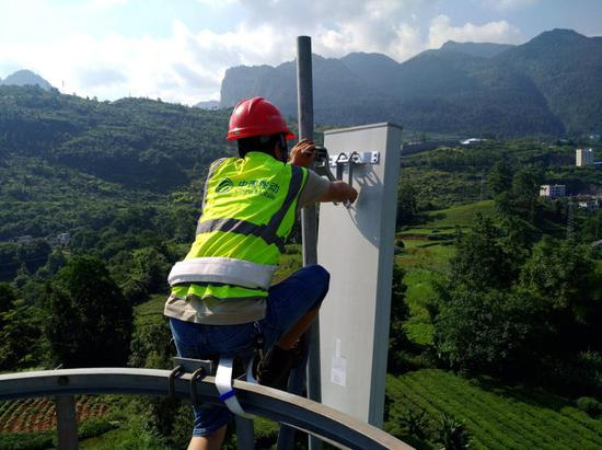 在湖北恩施,中國移動建設人員為偏遠鄉村基站更換天線。